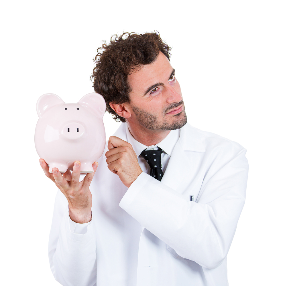 Closeup portrait, health care professional, scientist,  pharmacist, doctor, nurse knocking on piggy bank, listening to see if there is money, isolated on white background. Health care reform