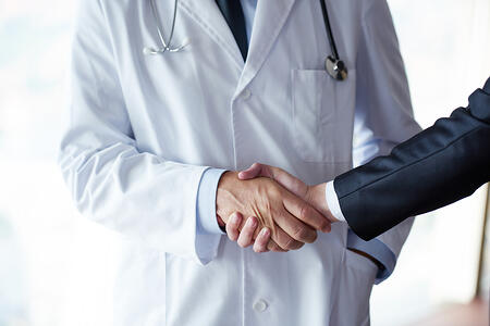 doctor handshake with a patient at doctors bright modern office in hospital-1
